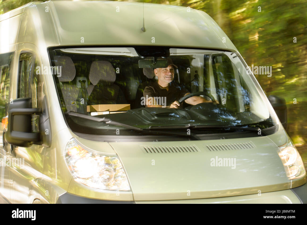 Postal delivery courier man driving cargo van delivering package - Stock Image