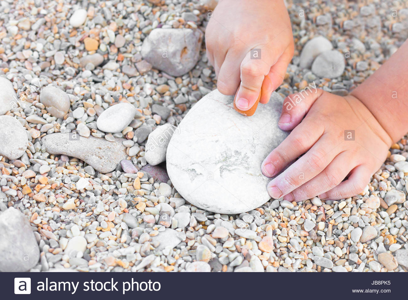 Close up of a young child's hands drawing on a stone Stock Photo