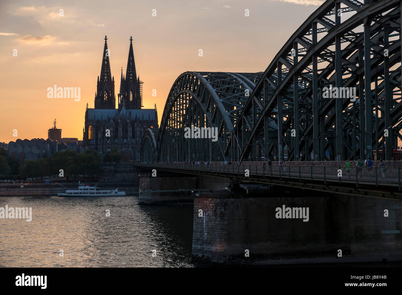 River Rhine at sunset, looking towards Cologne Cathedral (Kölner Dom) with the Hohenzollern Bridge Hohenzollernbrücke) Stock Photo