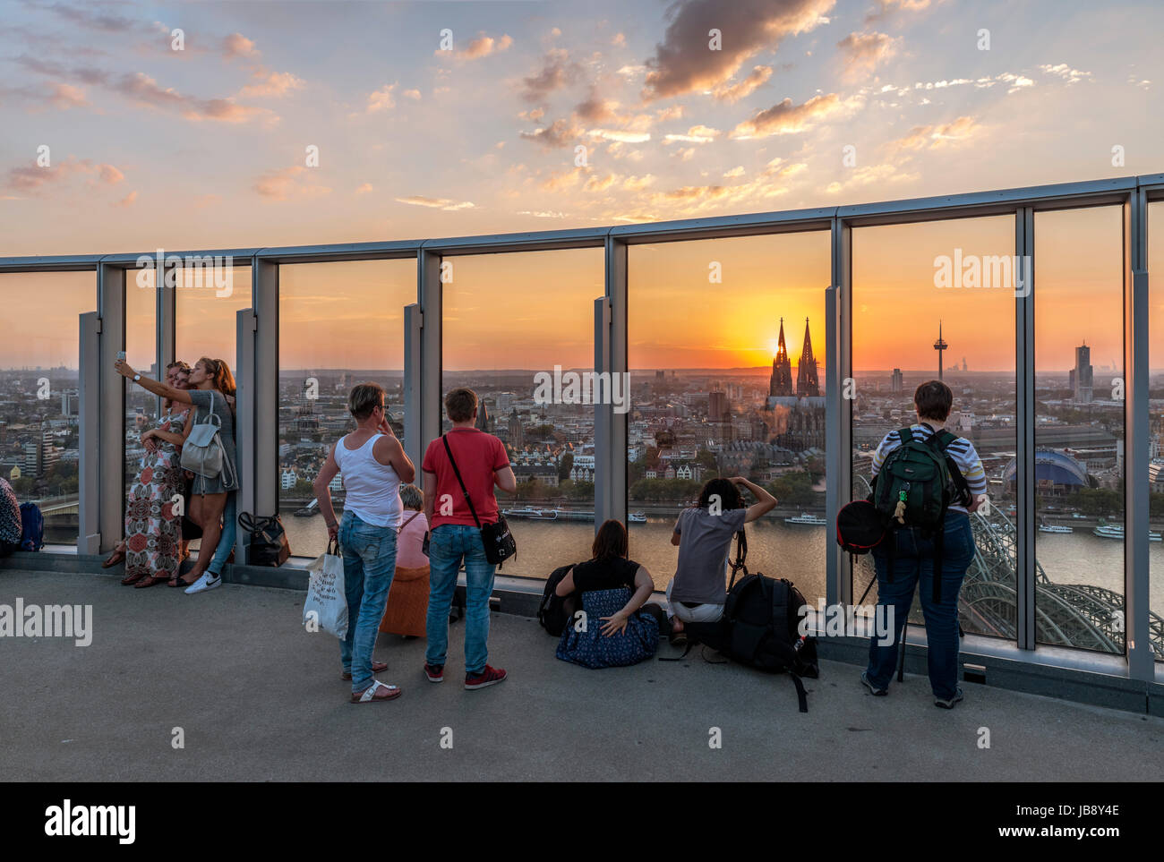 Tourists watching the sun set over Cologne Cathedral (Kölner Dom) from the top of the KölnTriangle, Cologne, - Stock Image