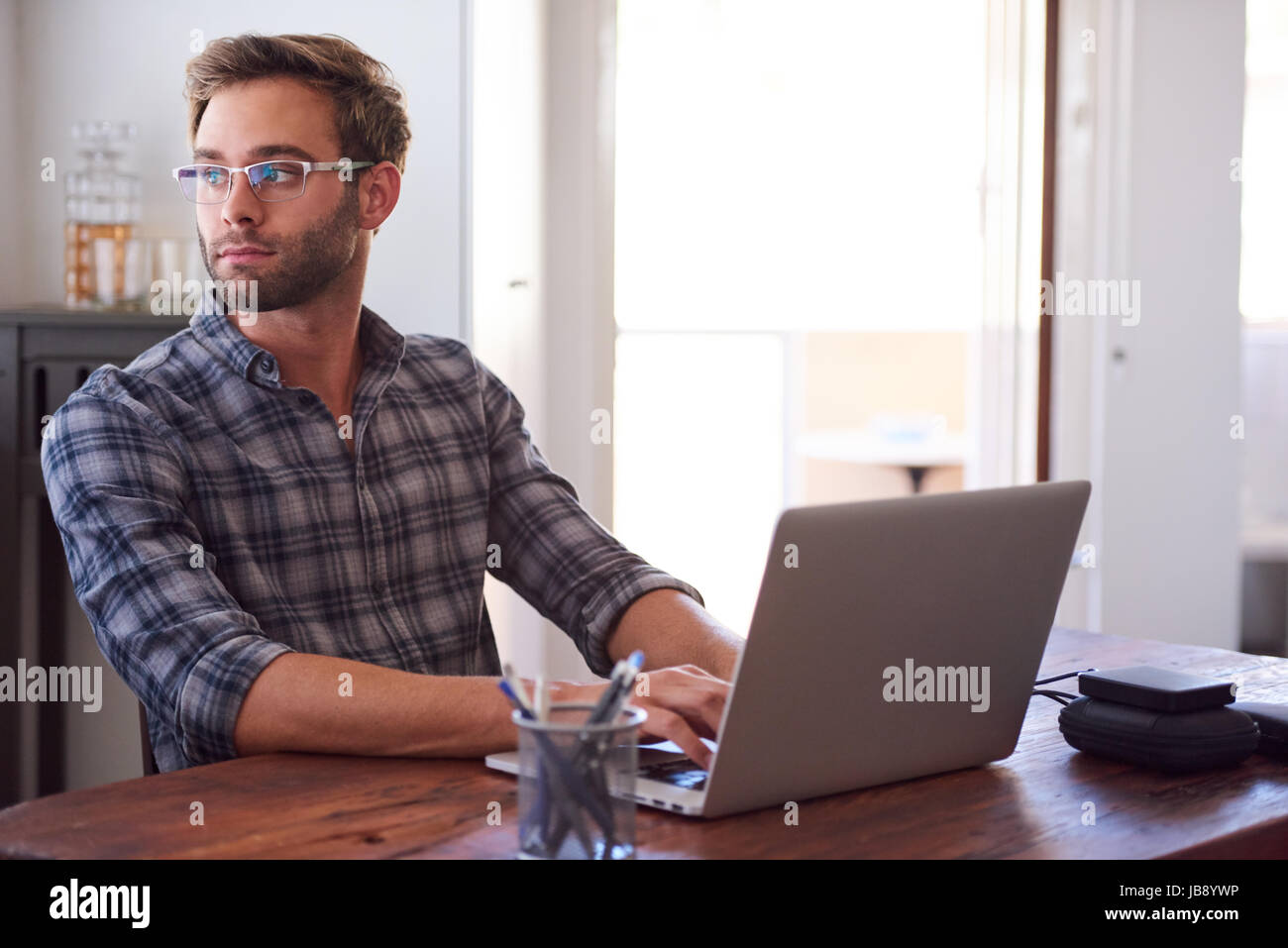 Successful young adult businessman looking back over his shoulder out of a whidow in thought with his hands still - Stock Image