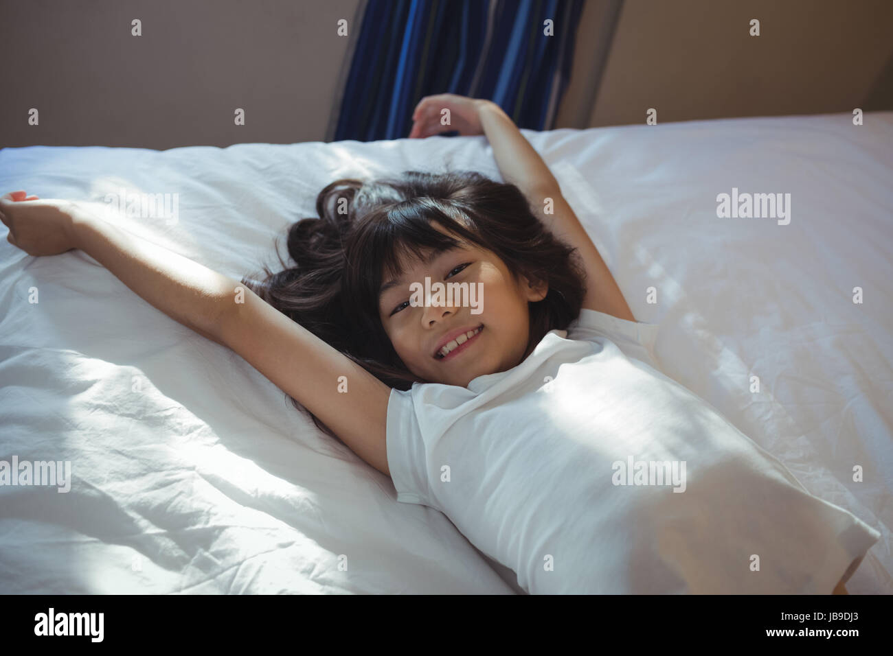 Portrait of cute girl lying on bed in the bed room at home - Stock Image