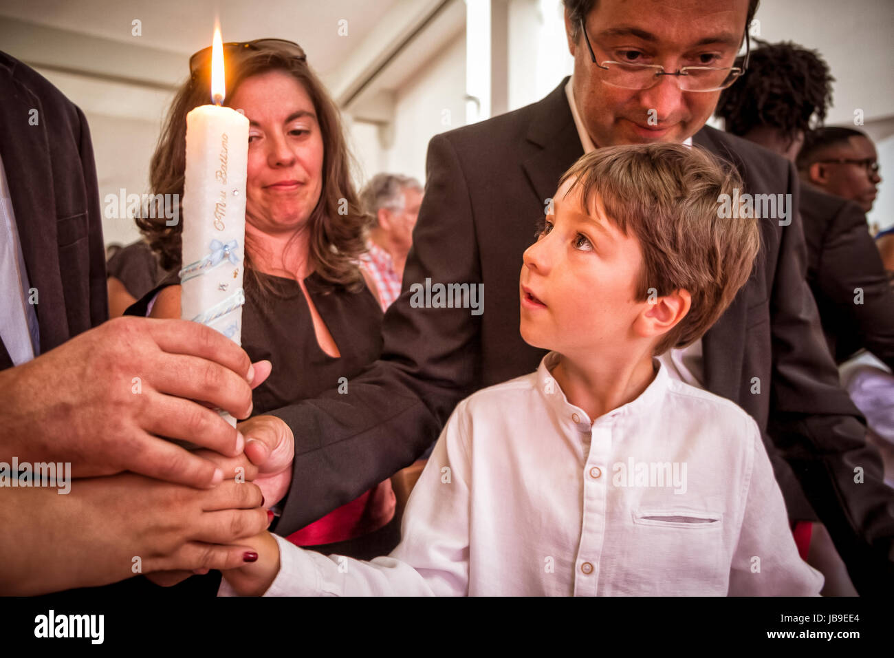 AMADORA/PORTUGAL-25 AUG 2015-Child picking up the candle of his baptism accompanied by the parents and godparents - Stock Image
