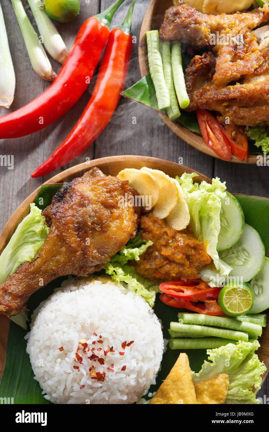 Popular Indonesian local food nasi ayam penyet, indonesian fried chicken rice. Fresh hot with steam smoke. Stock Photo