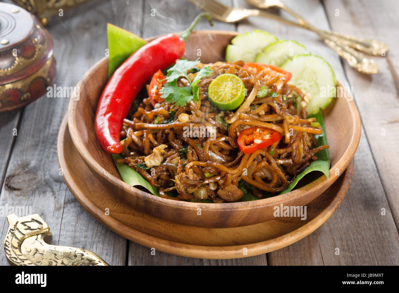 Mi goreng or mee goreng mamak Indonesian and Malaysian cuisine spicy fried noodles with wooden dining table setting. Fresh hot with steamed smoke. & Mi goreng or mee goreng mamak Indonesian and Malaysian cuisine ...