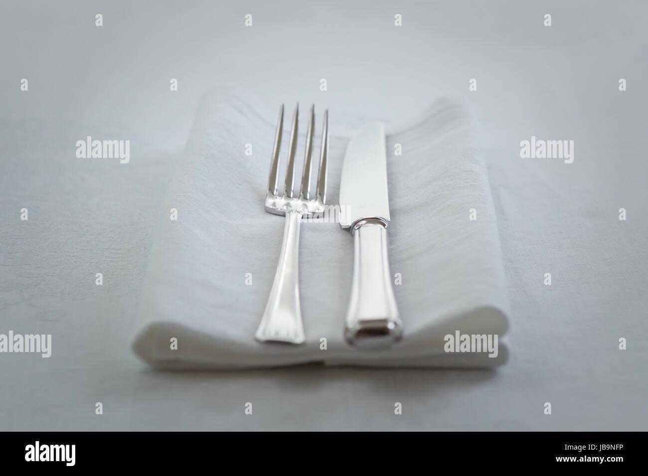 knife and fork on white napkin - Stock Image