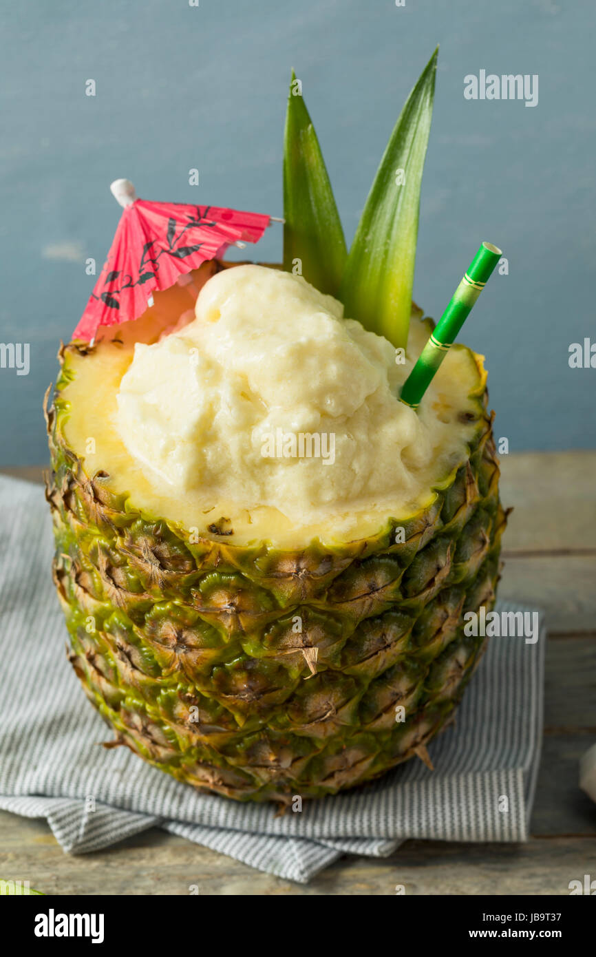 Frozen Pina Colada Cocktail in a Pineapple with a Garnish - Stock Image