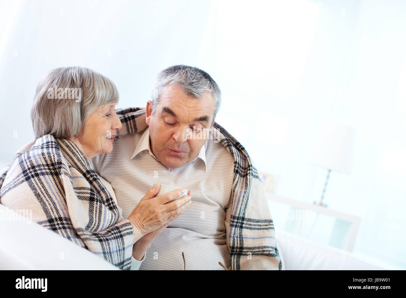Senior woman giving hot tea to her senior husband - Stock Image