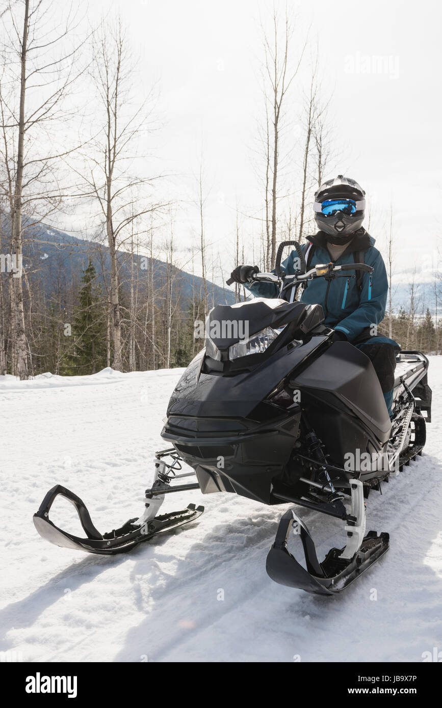 Man relaxing on snowmobile during winter - Stock Image