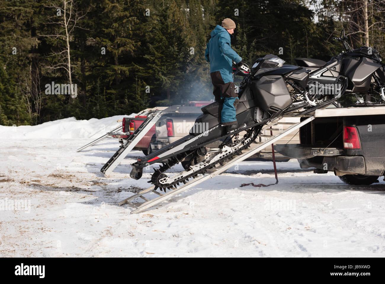 Man loading snowmobile on van during winter - Stock Image