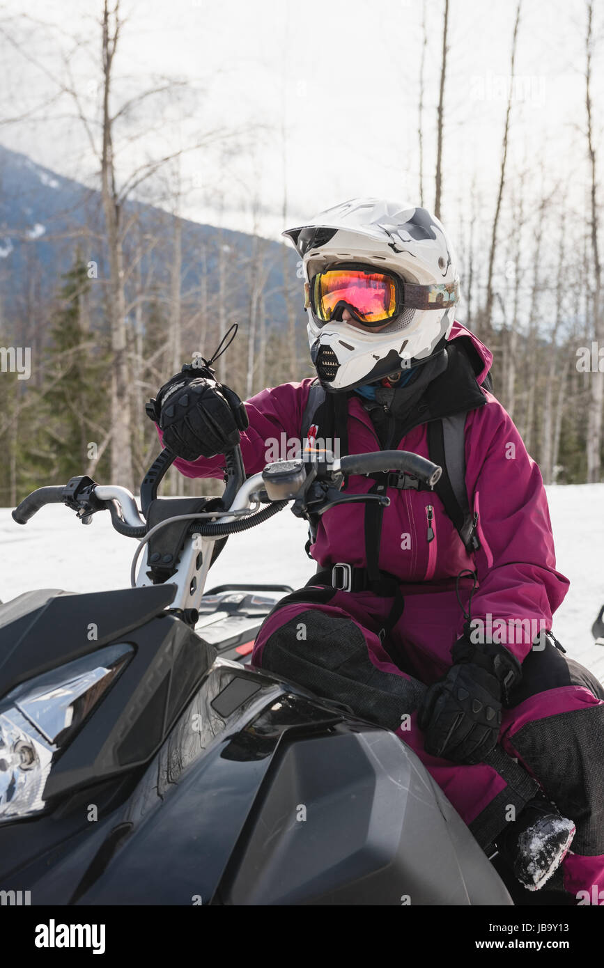 Woman relaxing on snowmobile during winter - Stock Image