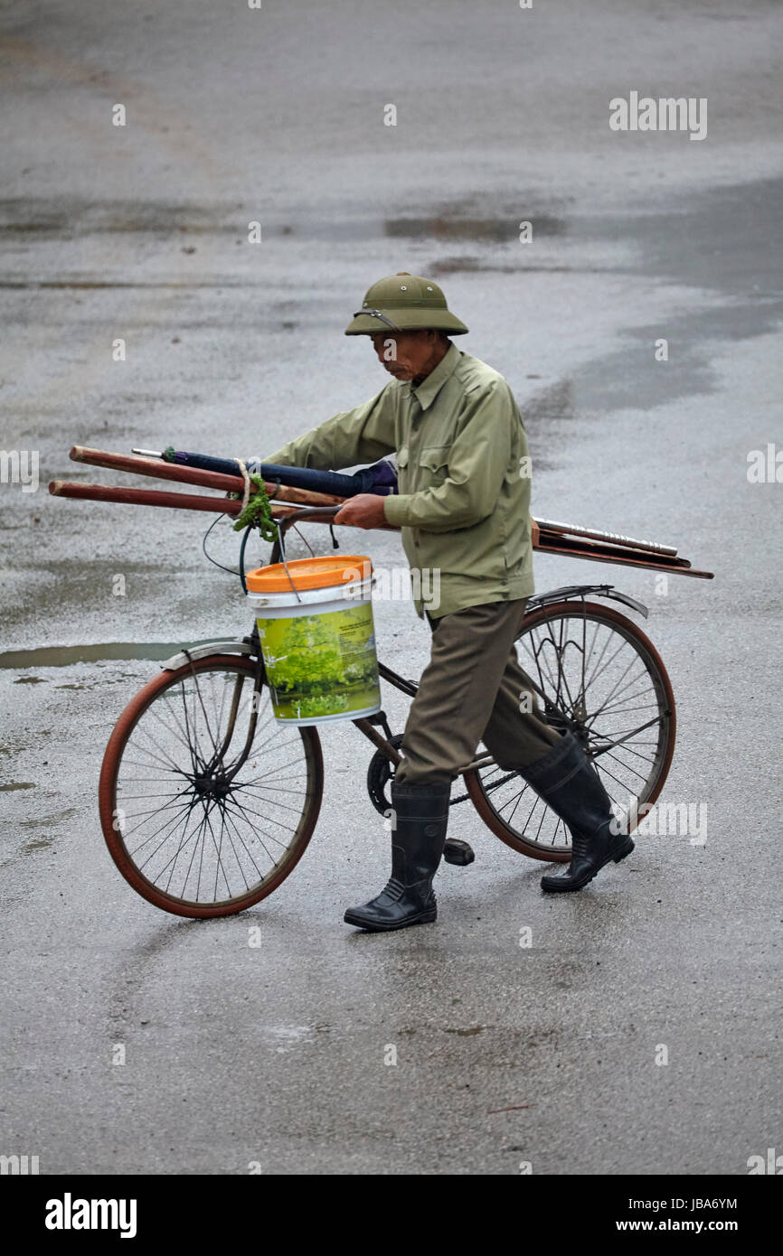 Old man and cycle in the rain, Ninh Binh, Vietnam - Stock Image