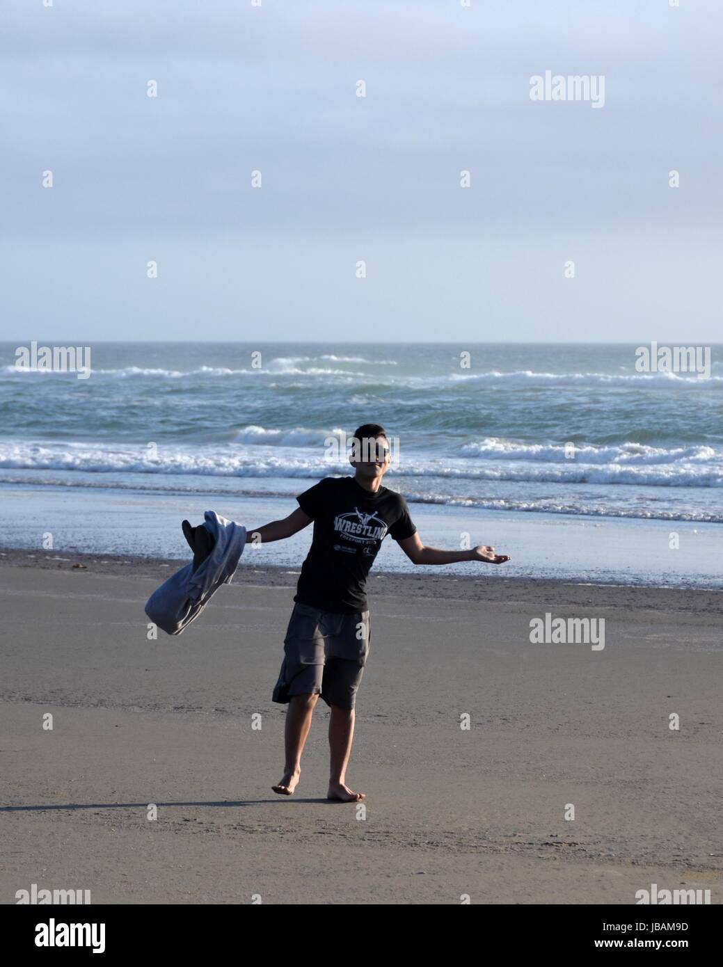 Teenager Standing On Beach Gives A Carefree Shrug - Stock Image