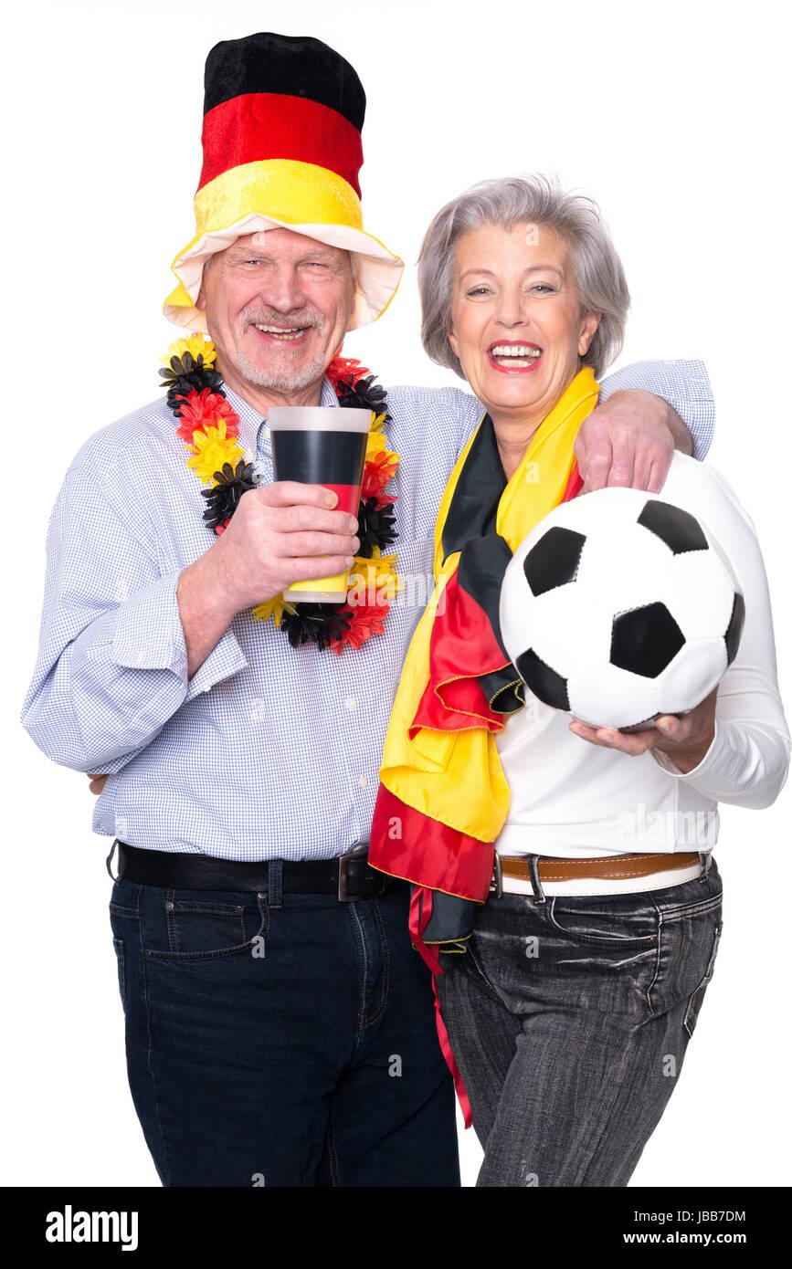 Senioren als Fußballfans vor weißem Hintergrund - Stock Image