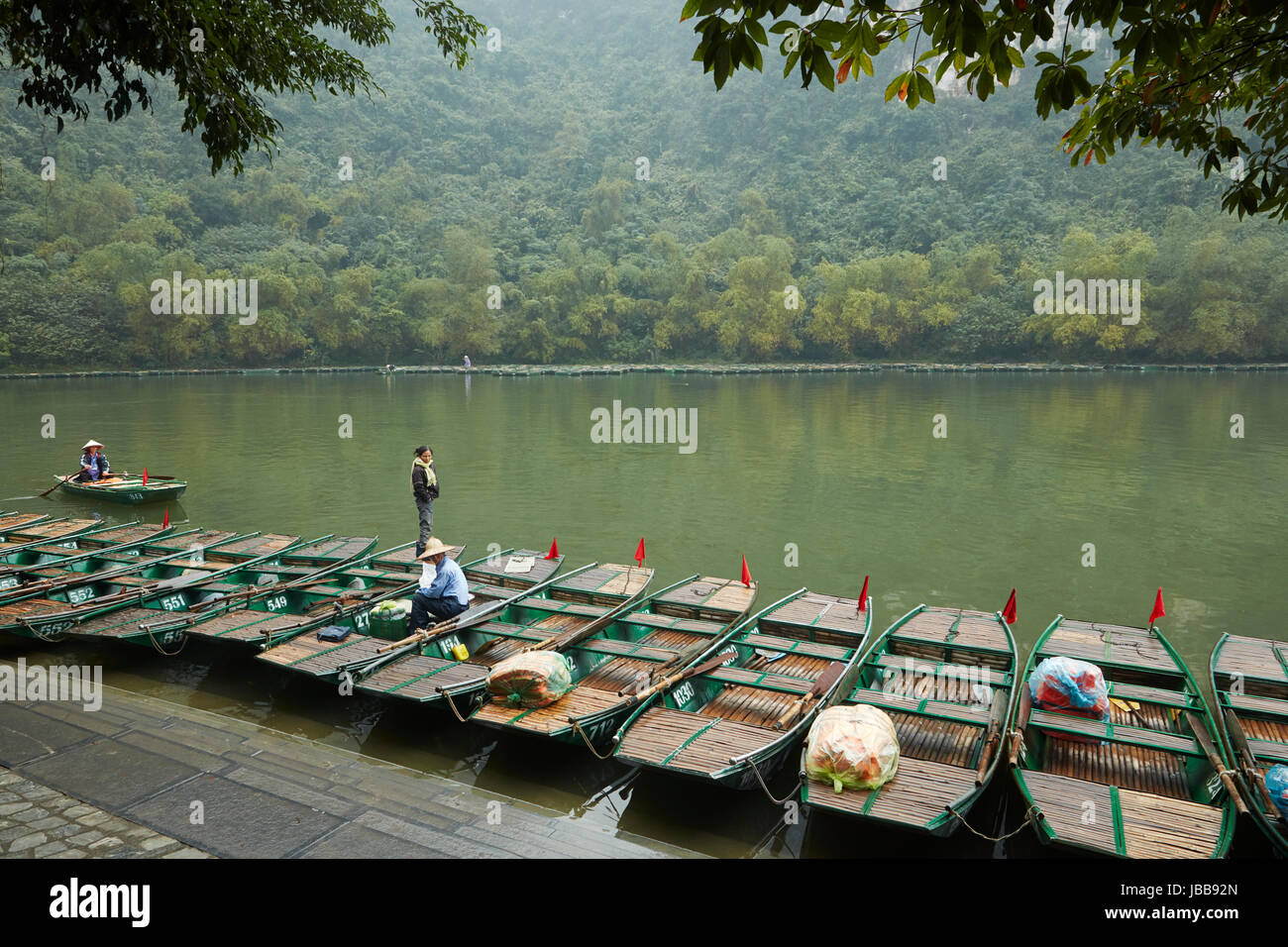Tourist boats for Trang An Grottoes trip (UNESCO World Heritage Area), near Ninh Binh, Vietnam - Stock Image