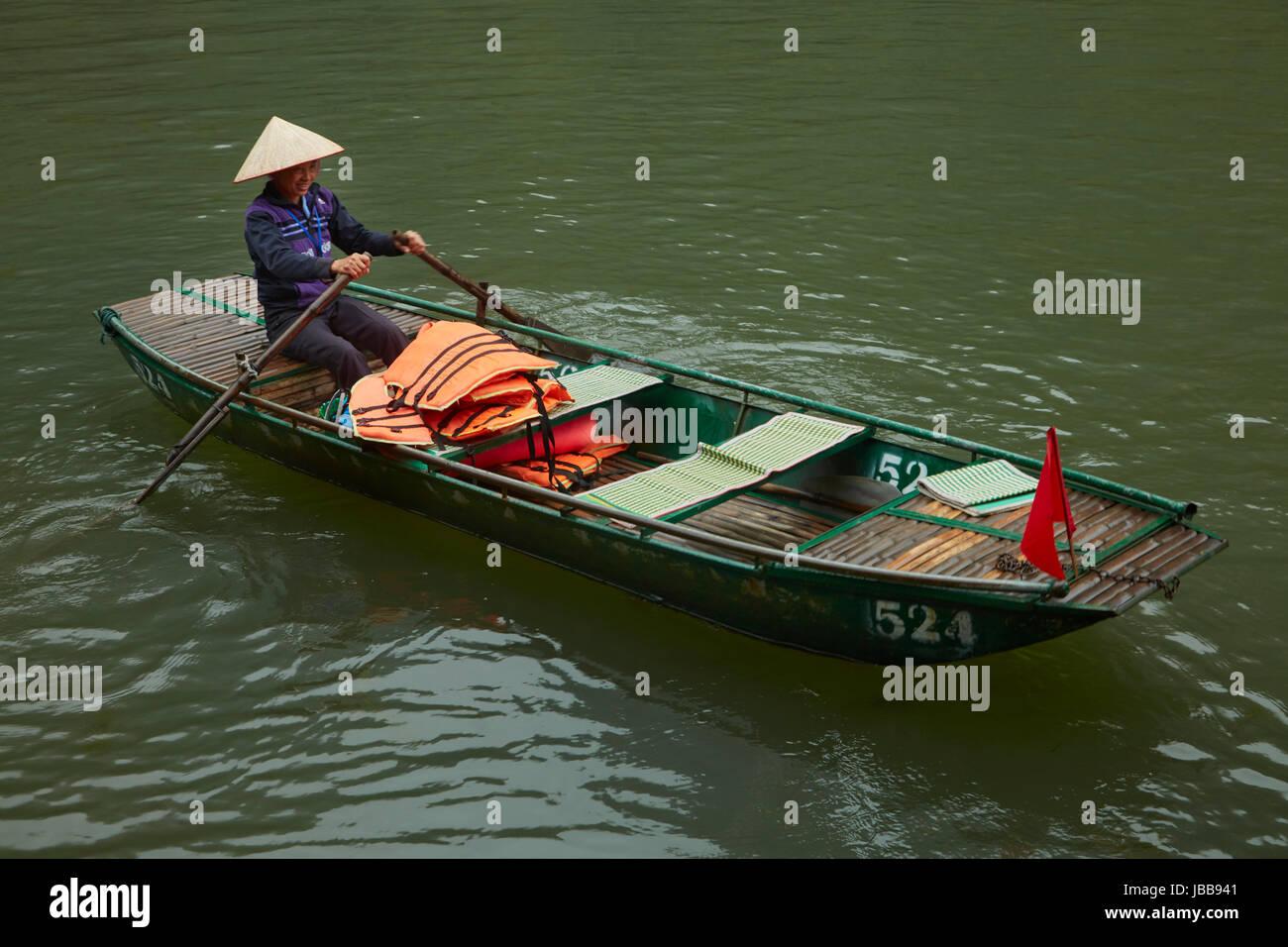 Woman in tourist boat for Trang An Grottoes trip (UNESCO World Heritage Area), near Ninh Binh, Vietnam - Stock Image