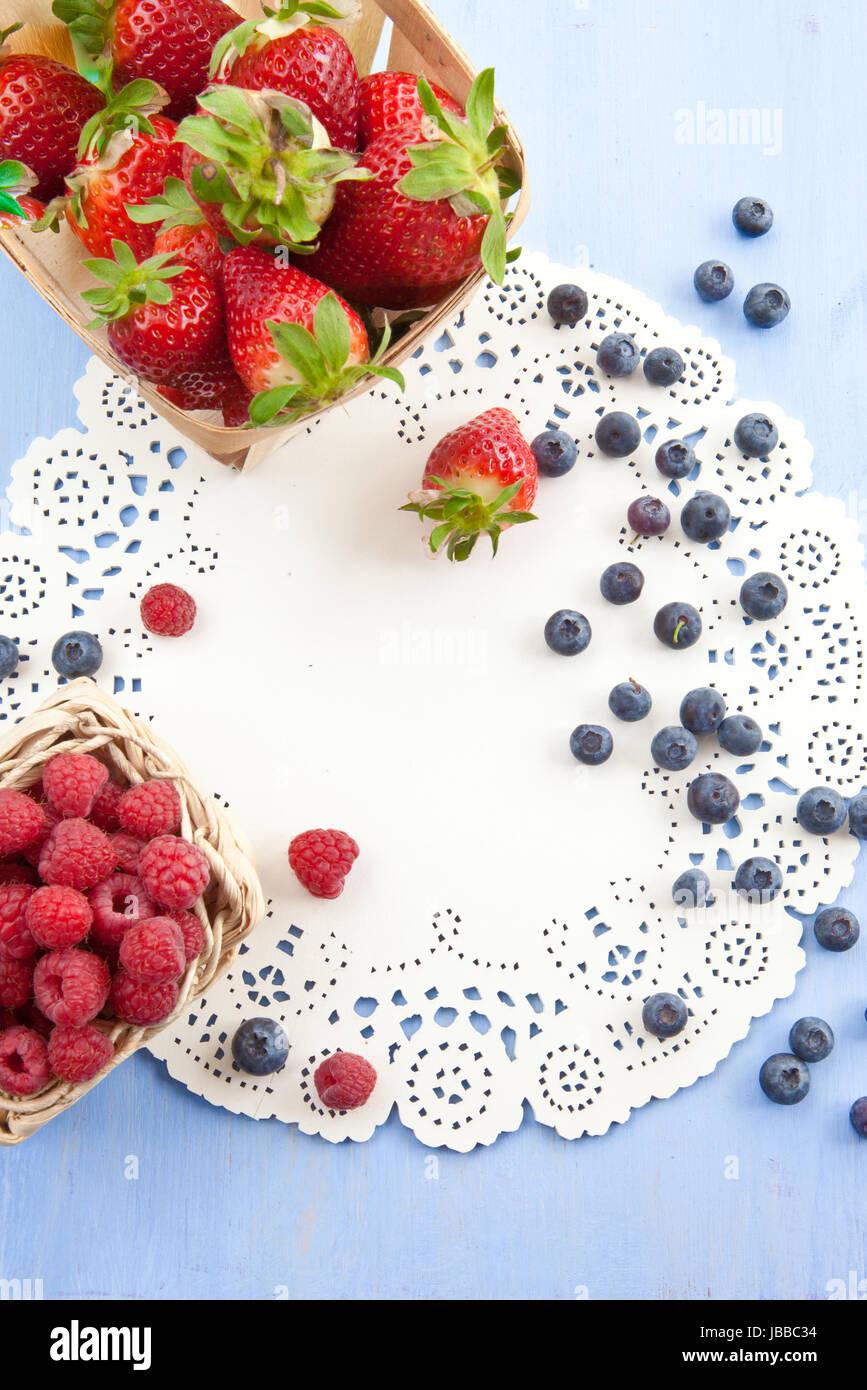 Frische Erdbeeren, Himbeeren und Blaubeeren auf blauem Hintergrund Stock Photo