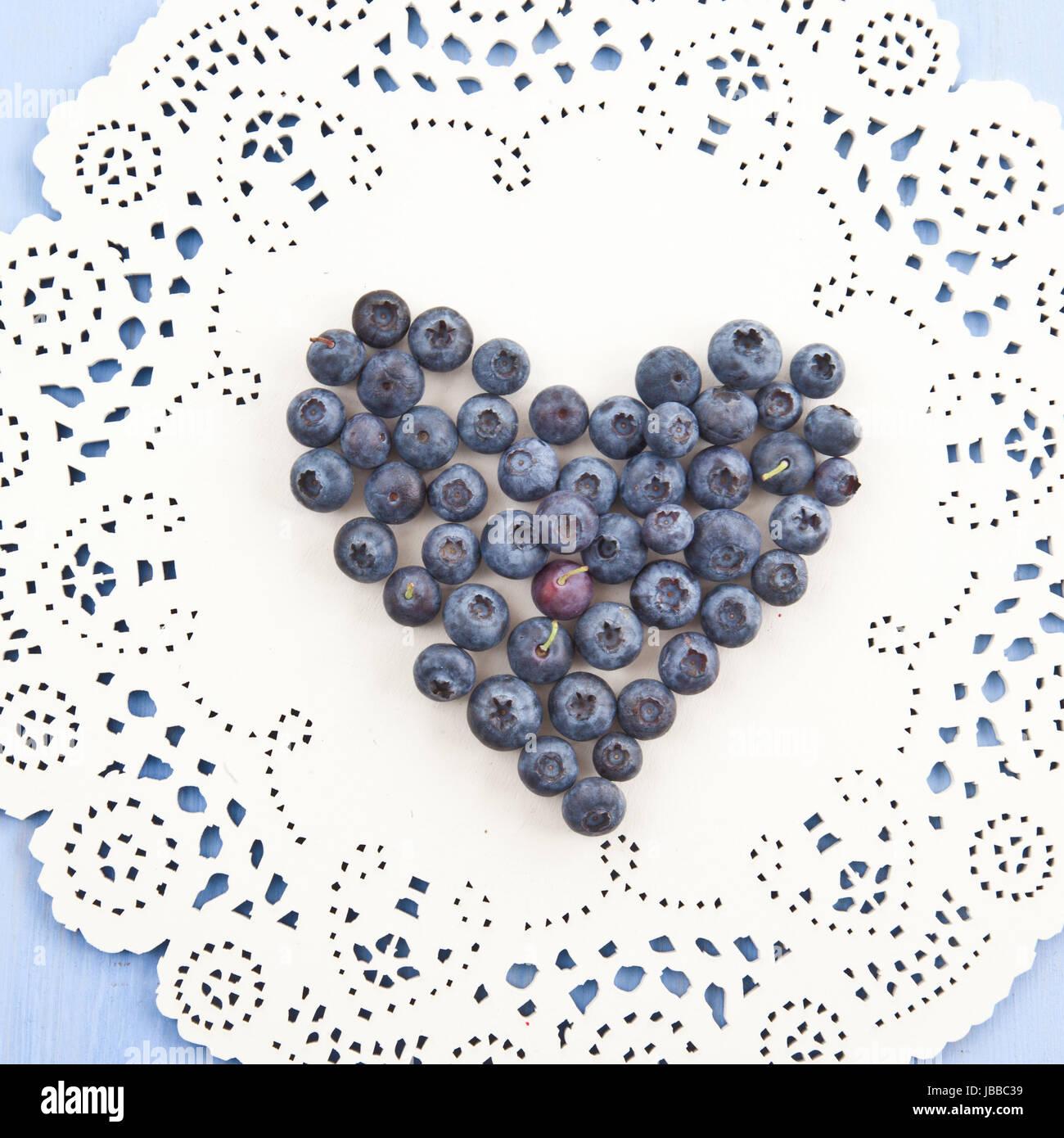 Frische Heidelbeeren in Herzform auf dekorativem Hintergrund Stock Photo
