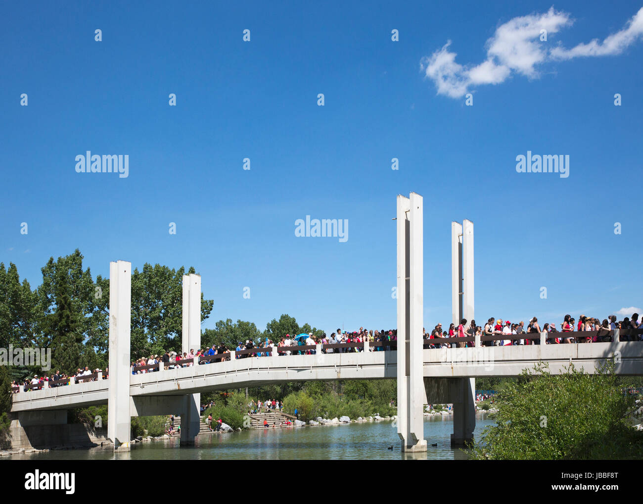 Canada Day crowds on bridge over lagoon between Prince's Island and Eau Claire in downtown Calgary - Stock Image