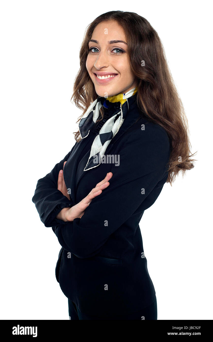 Casual shot of cheerful air stewardess standing sideways, arms folded. Stock Photo