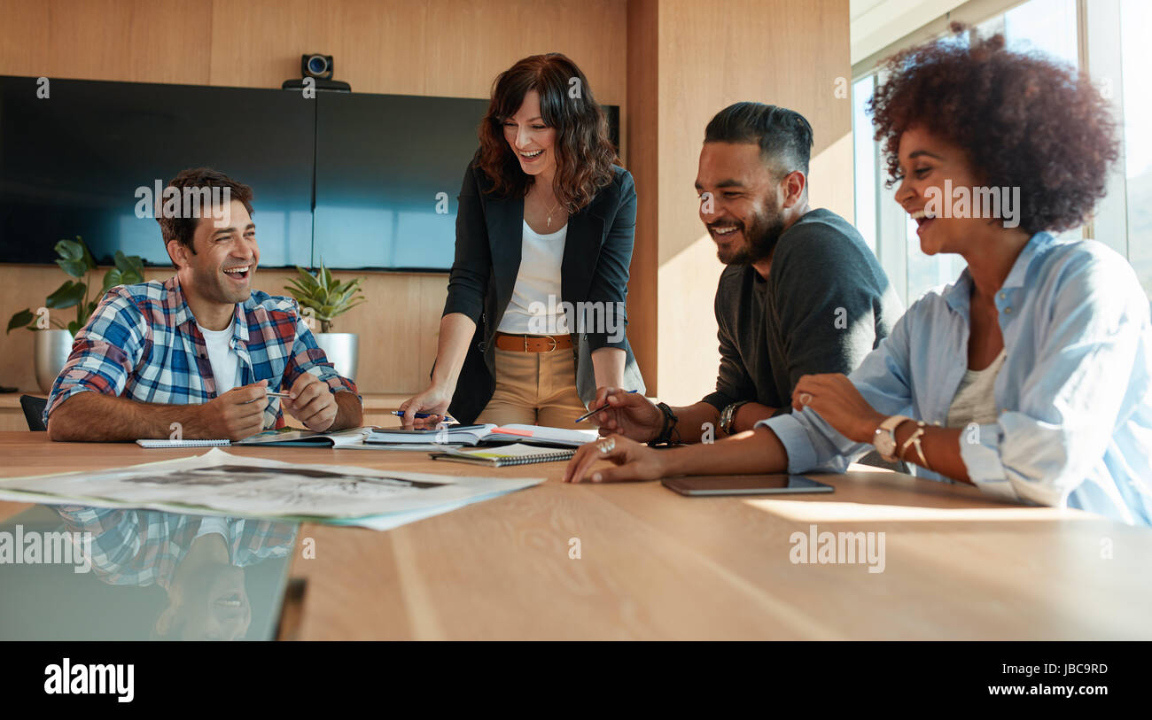 Shot of coworkers discussing in meeting room at creative office. Office workers discussing new business plan together - Stock Image