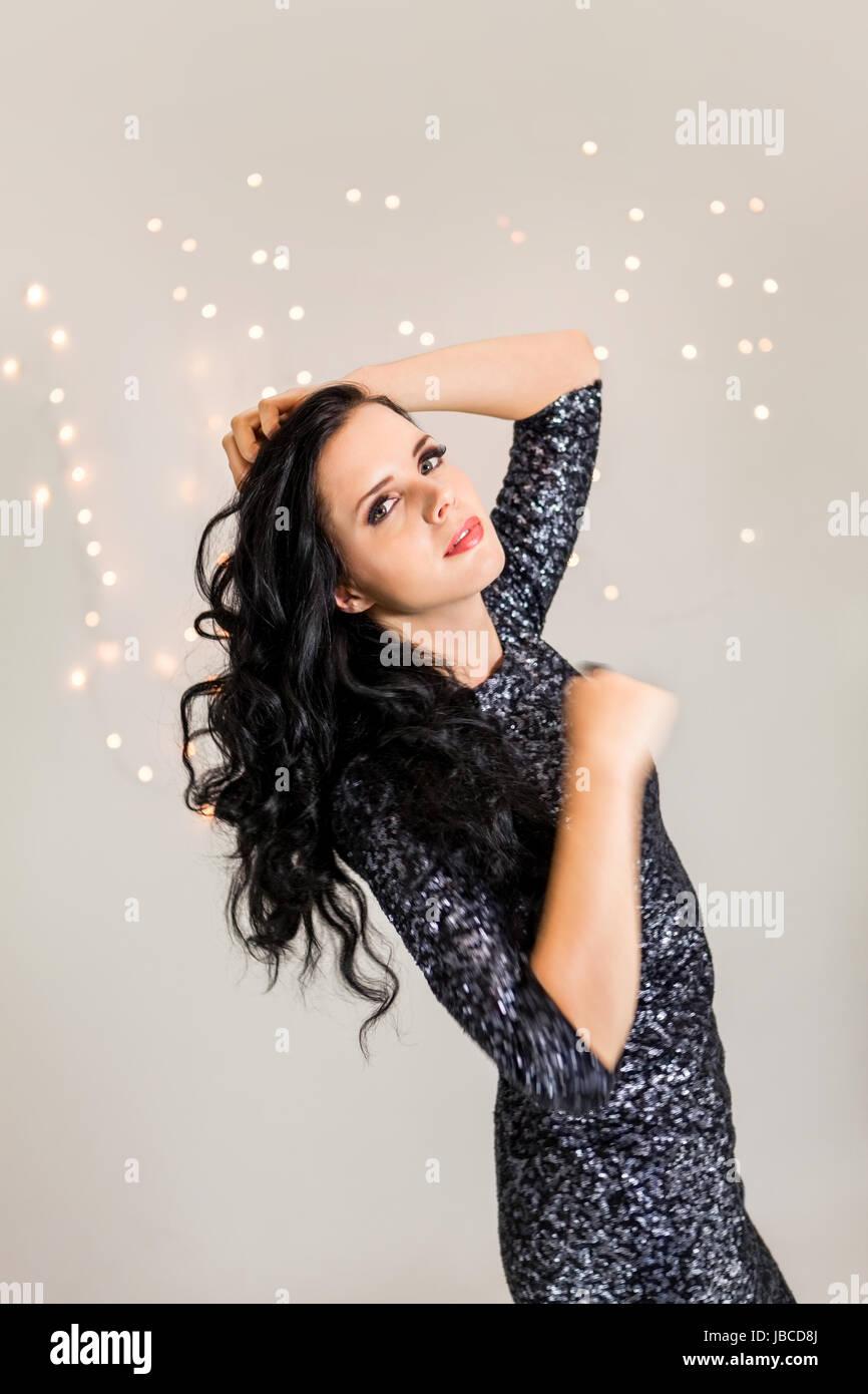 attraktive junge dunkelhaarige frau mit abendgarderobe am tanzen party feiertag glitzer kleid bokeh Stock Photo