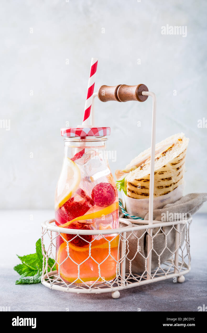 Fresh lemon and raspberry lemonade with homemade sandwich with ham, cheese and lettuce with. Healthy picnic food. - Stock Image