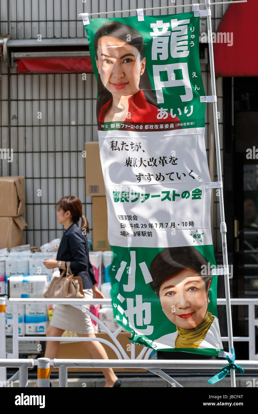 Tokyo, Japan. 10th June, 2017. A woman walks a banner from the political party Tomin First no Kai during a campaign - Stock Image