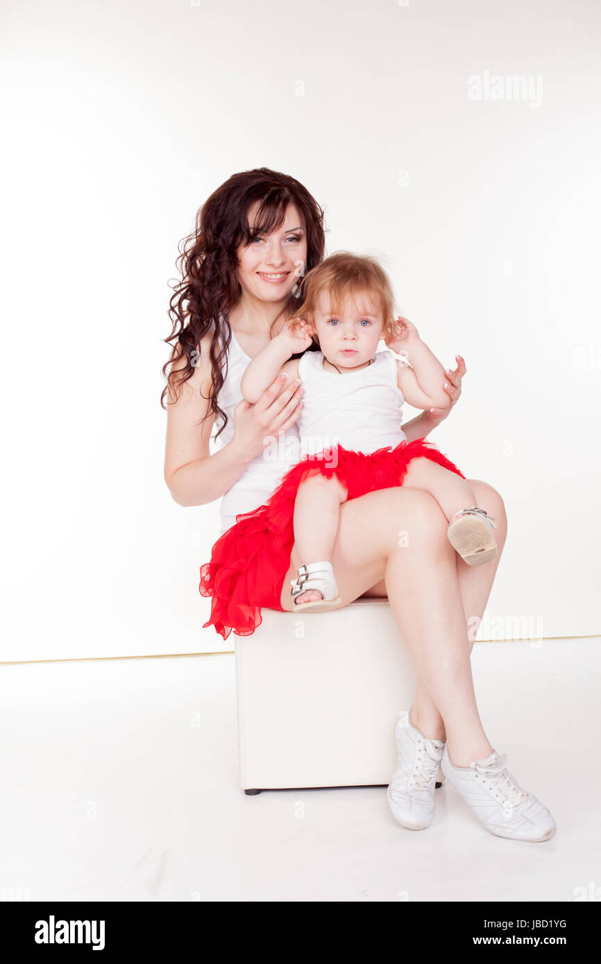 mother and little daughter in red skirts - Stock Image