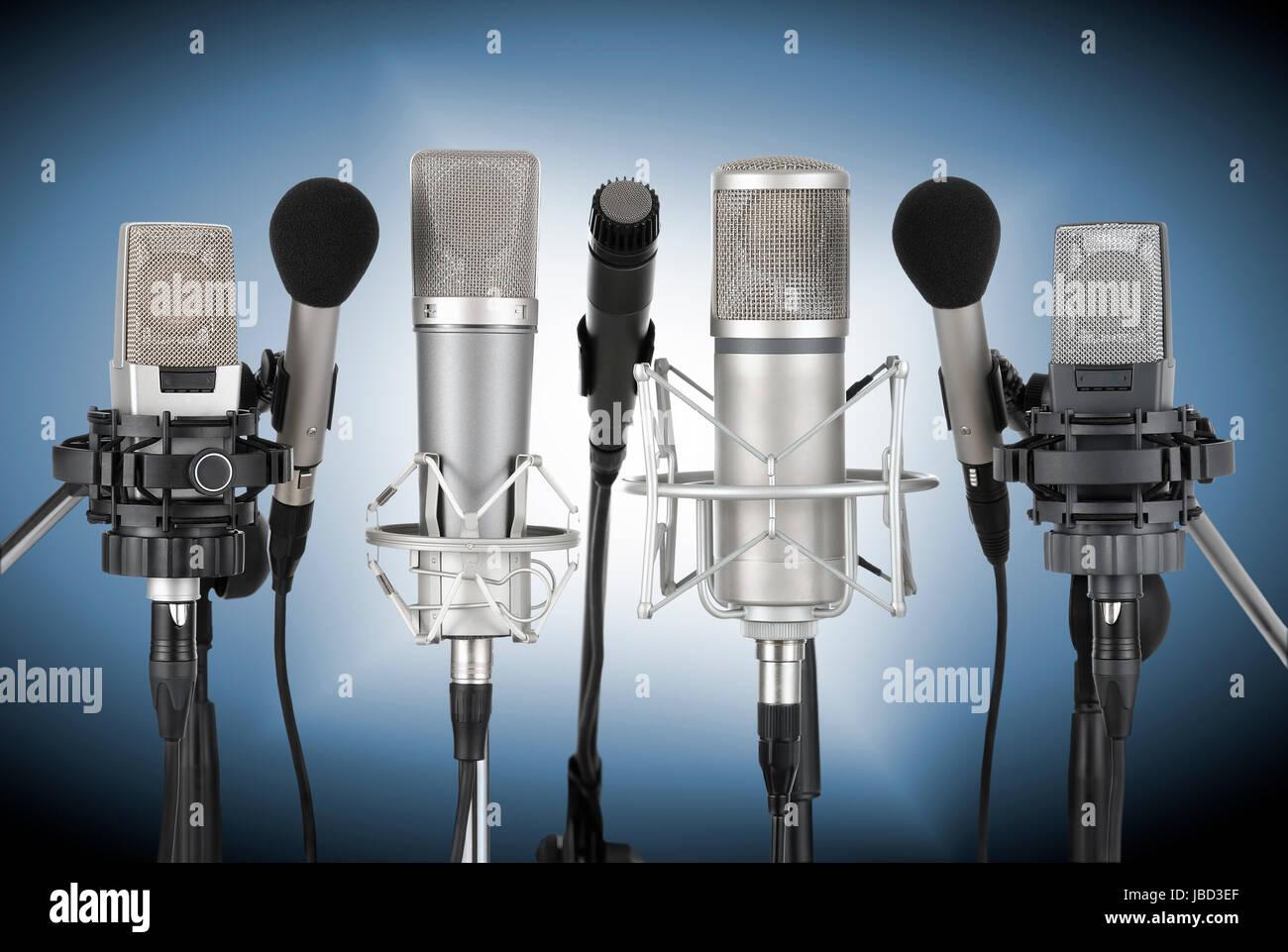 Studioaufnahme von einem Set professioneller Mikrofone vor blau verlaufendem Hintergrund - Stock Image