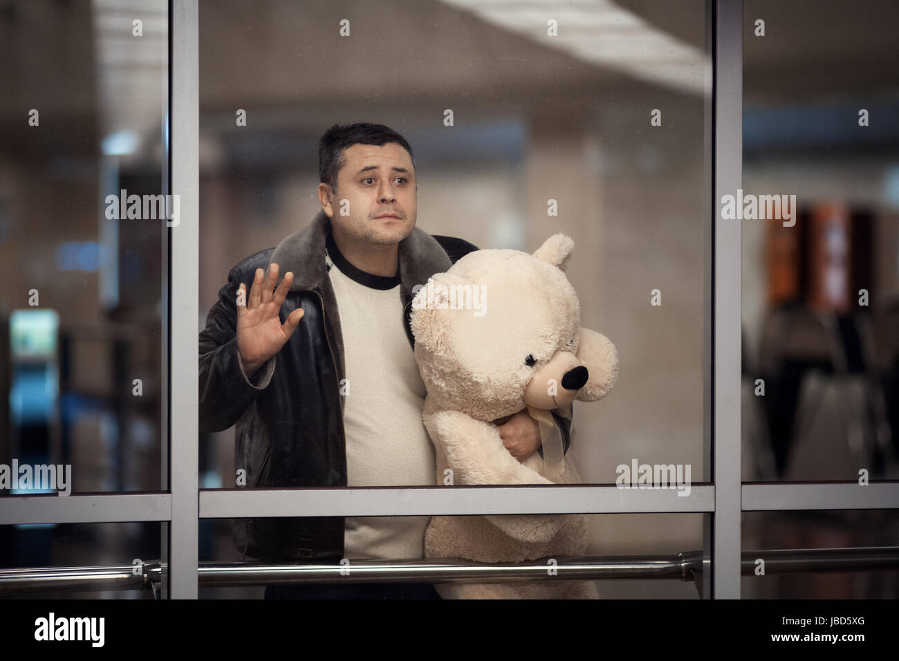 Man is holding a toy bear and looking sadly into the distance. He says goodbye. - Stock Image