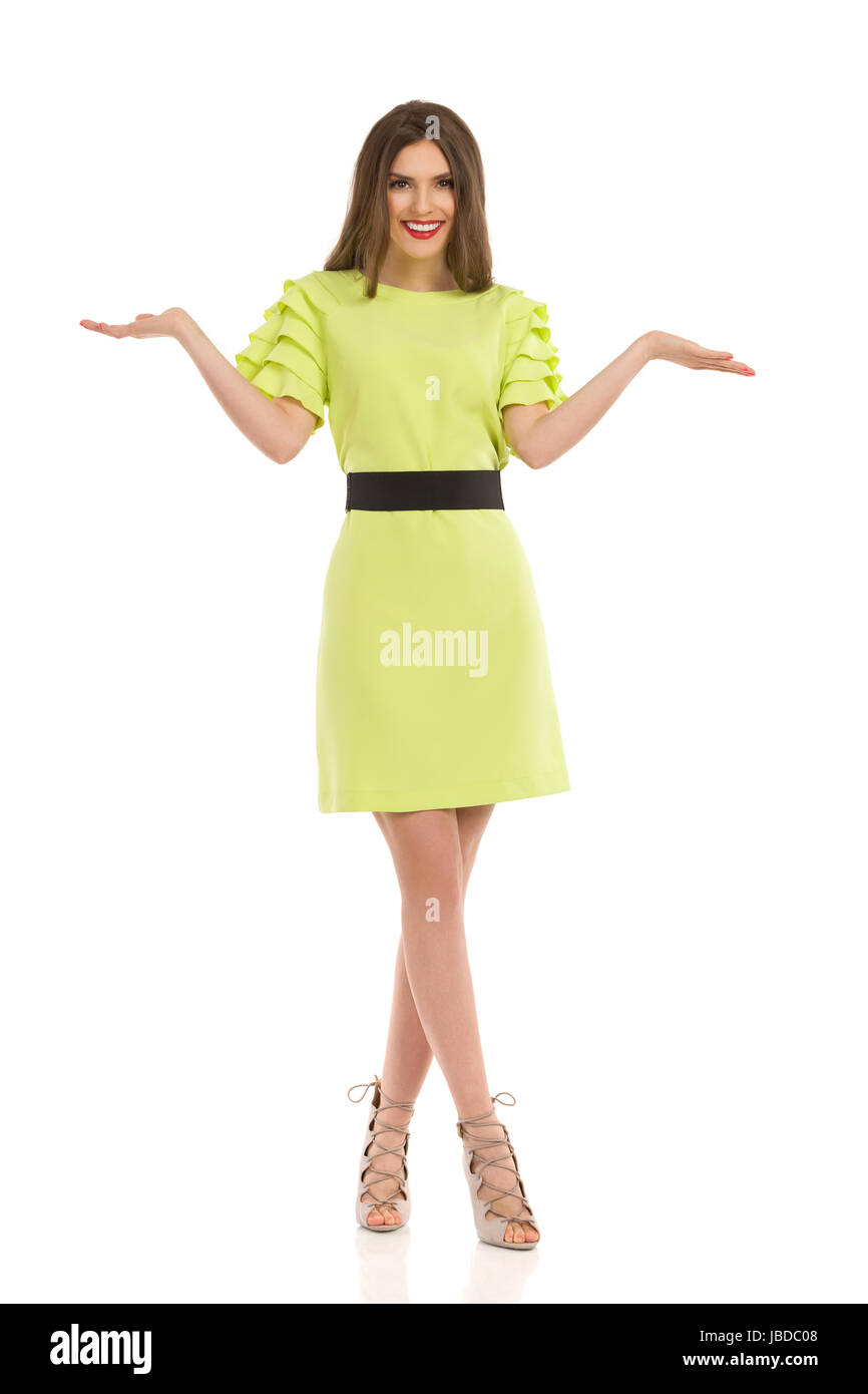 Beautiful woman in lime green dress and high heels is posing with hands raised, comparing or showing something, - Stock Image