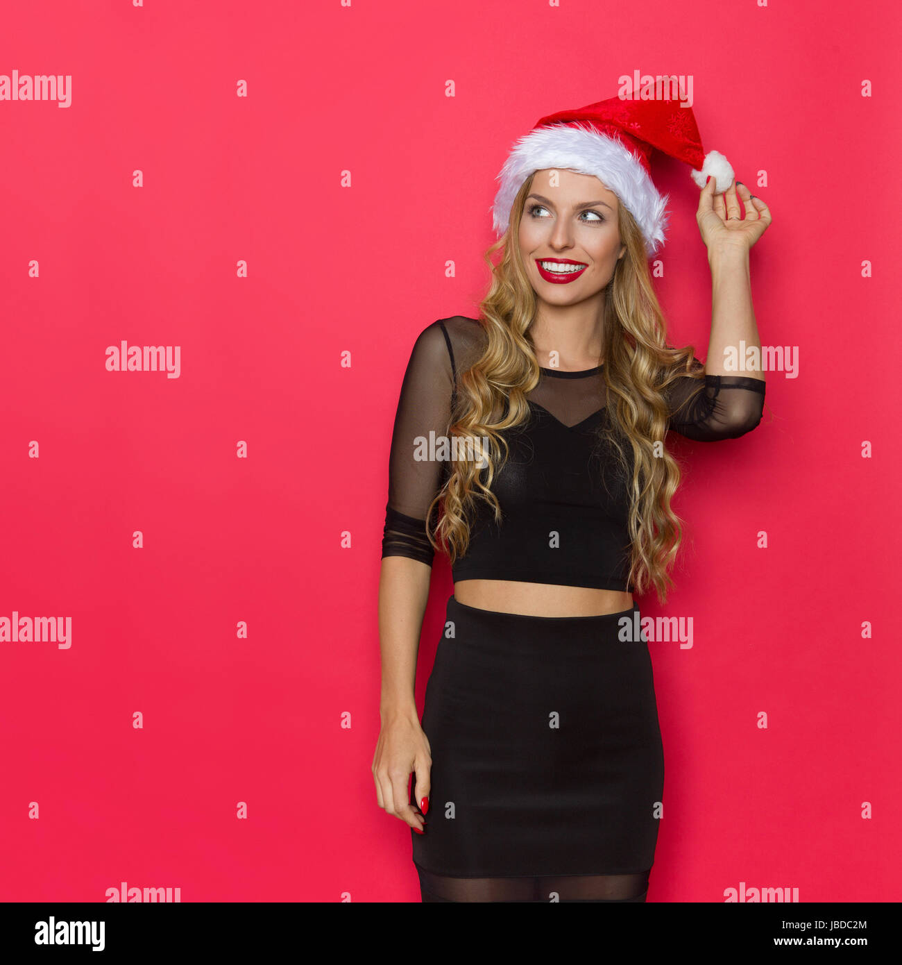 Smiling young blond woman in santa hat and black dress watching. Three quarter length studio shot on red background. Stock Photo