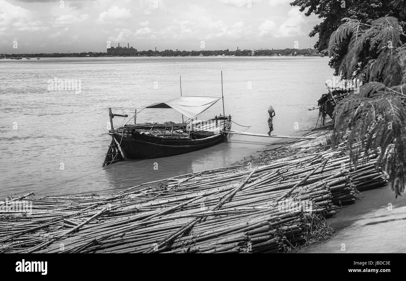Man walks wooden plank to unload dredged sand from river Hooghly used in Durga Puja festival. - Stock Image