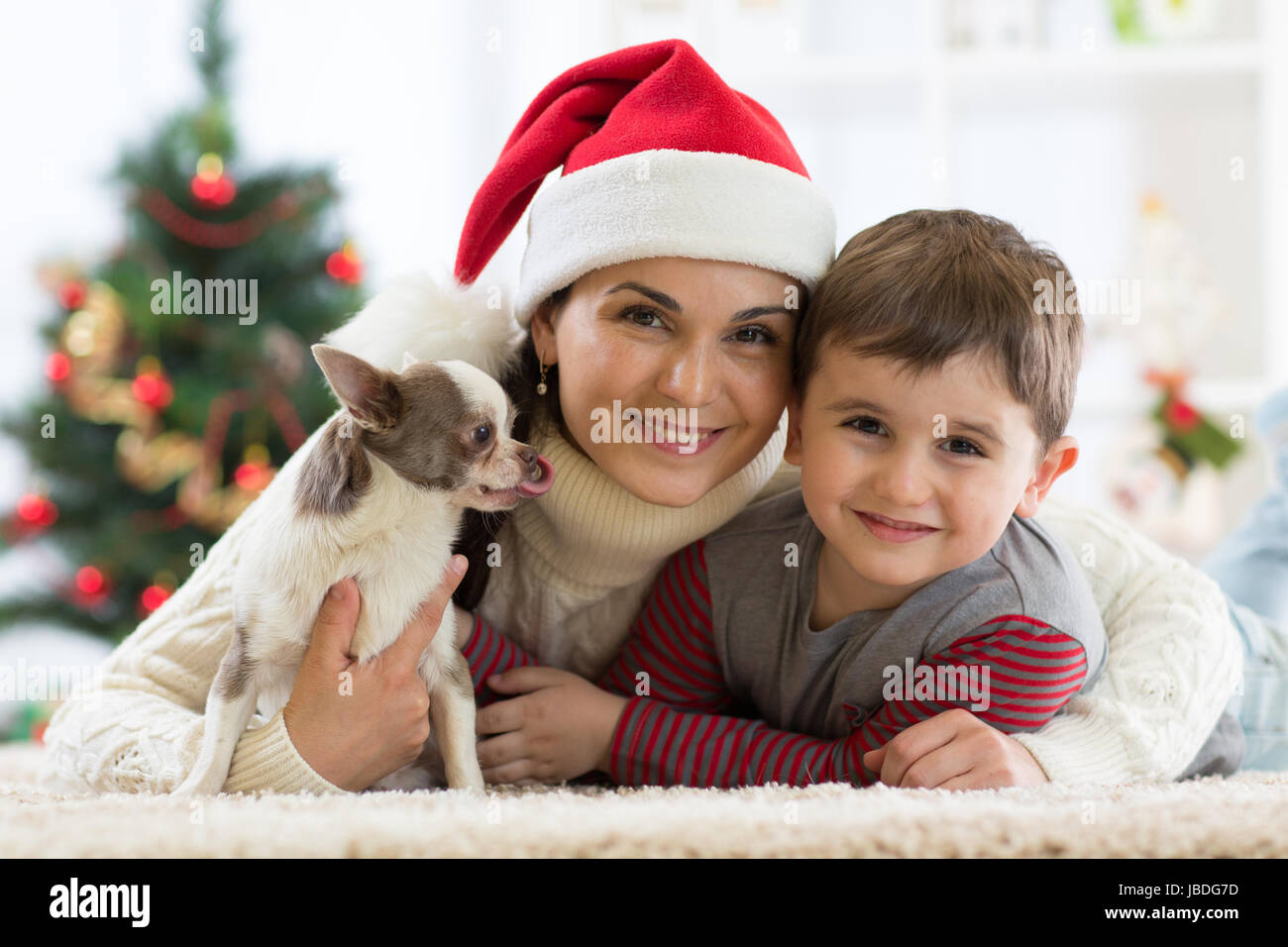 Portrait of a happy family and the dog spending together Christmas time at home near the x-mas tree Stock Photo