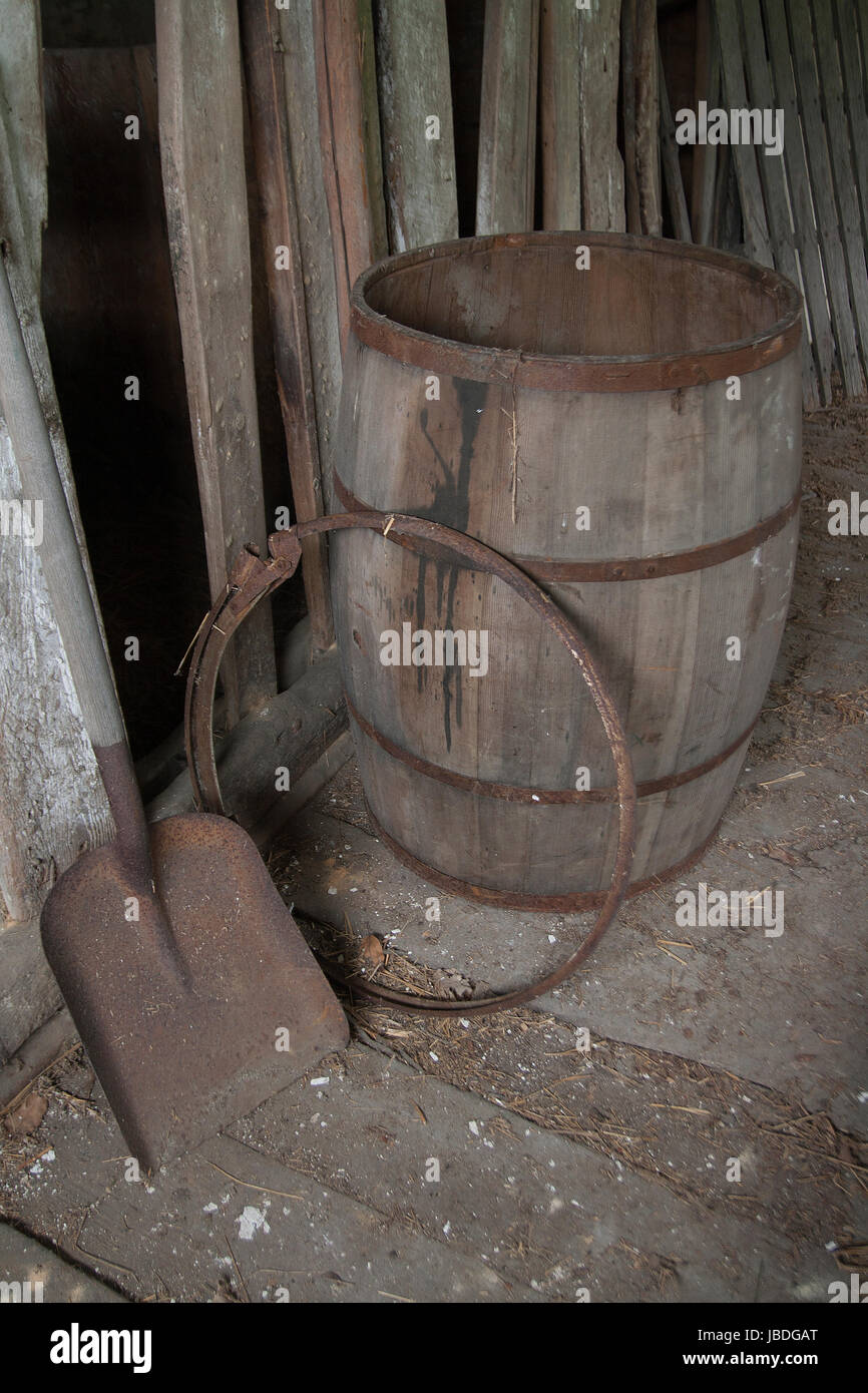 Antique barrel and shovel abandoned in an old wooden barn. - Stock Image