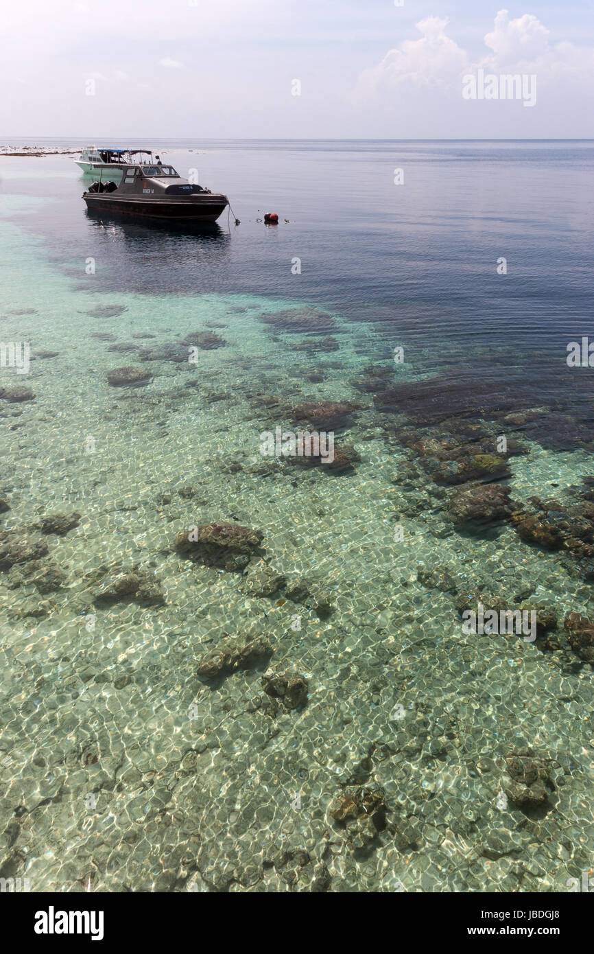 SIPADAN, BORNEO, MALAYSIA - A boat floating in front of coral reef. Stock Photo