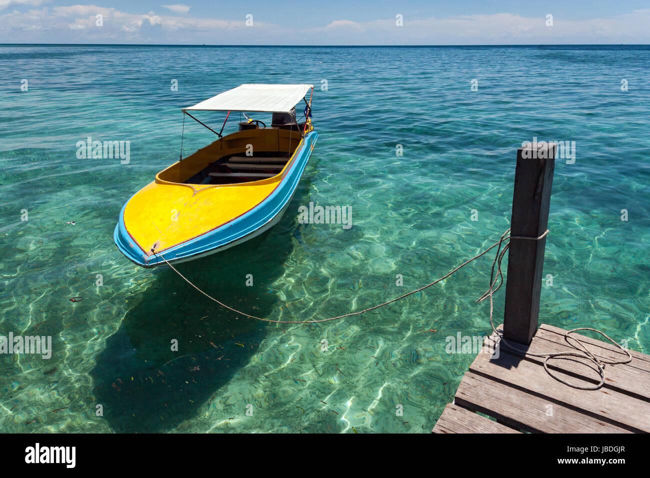 SIPADAN ISLAND, BORNEO, MALAYSIA - Colourful boat floating in calm crystal clear water. Stock Photo