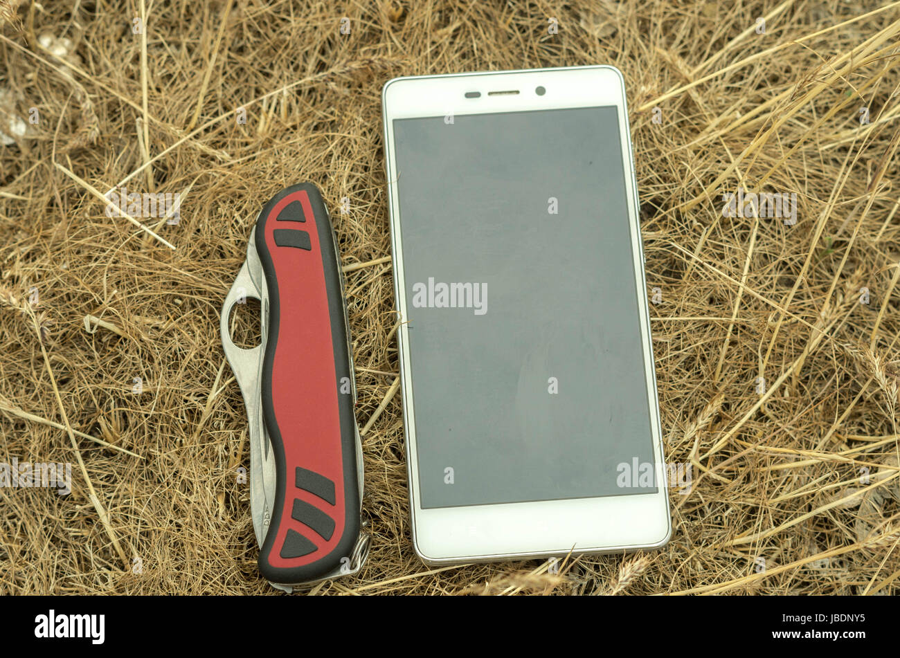 Mobile phone and knife in the manger. Multi-functional knife. - Stock Image