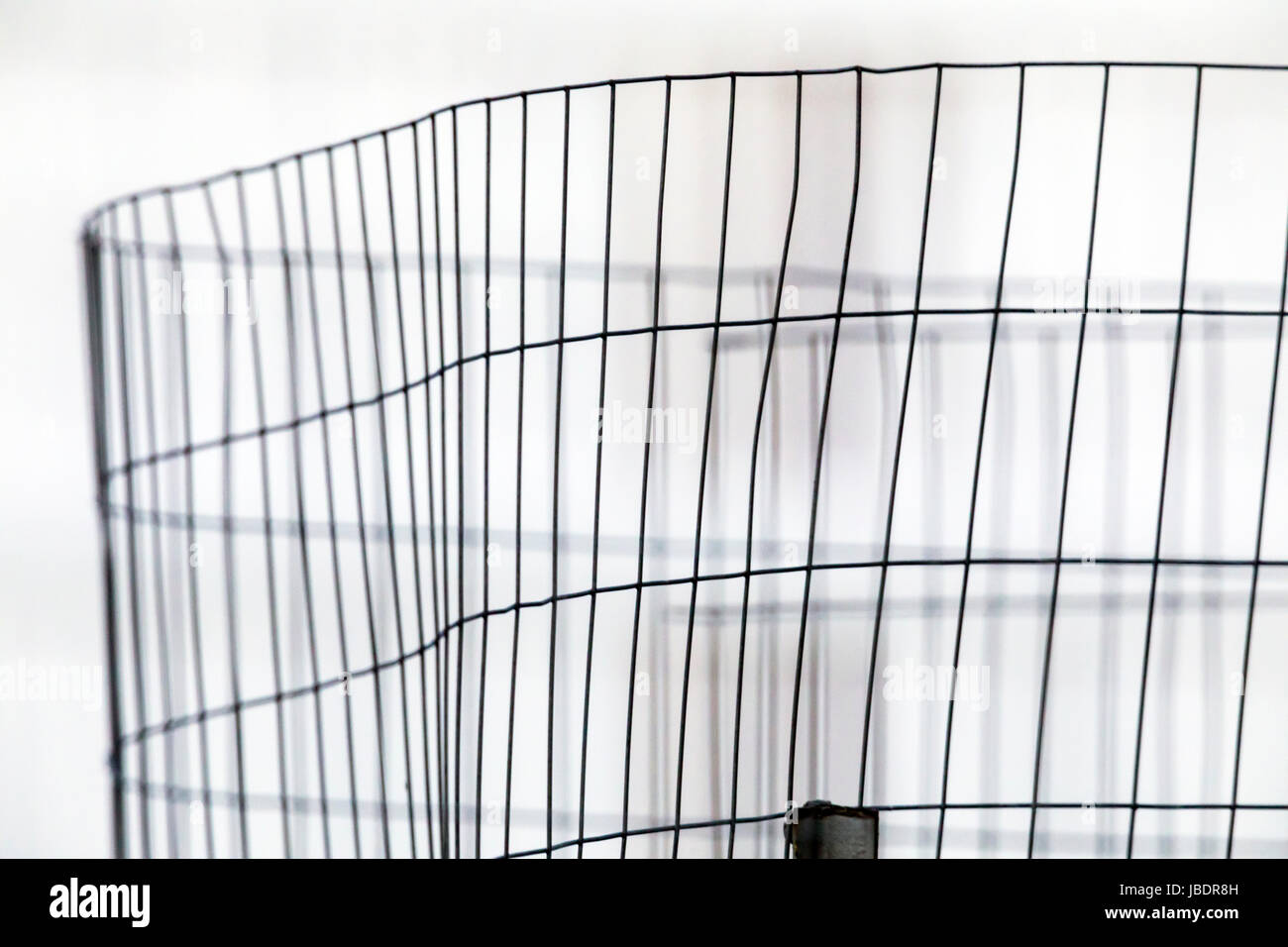 Wire mesh garden fence casts abstract shadows on white wall Stock ...
