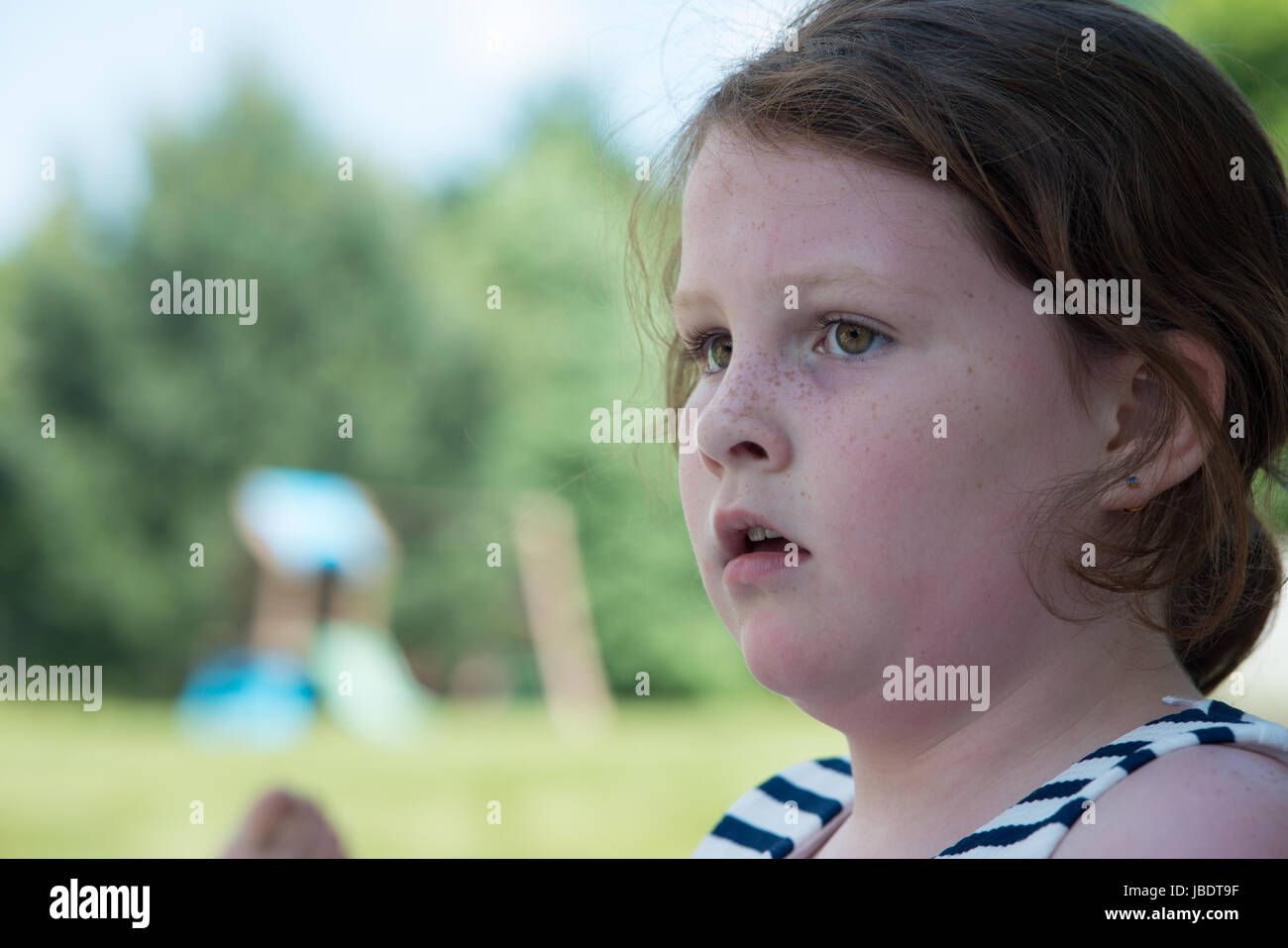 Close Portrait of Young Girl Looking Concerned Outside - Stock Image