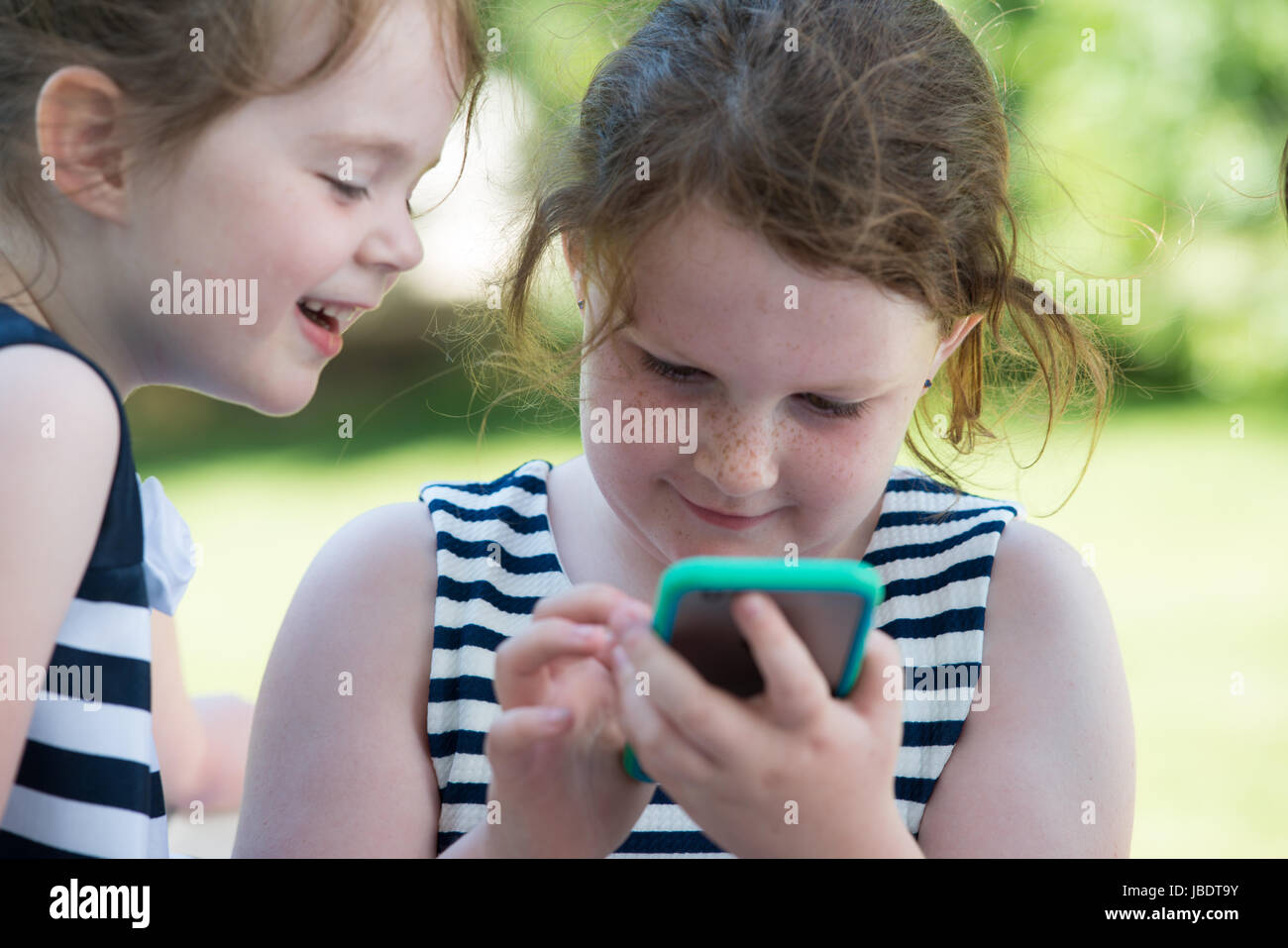 Happy Laughing Children Playing with Smartphone Outside - Stock Image