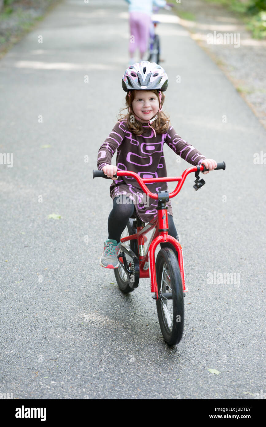 Young Girl Riding Bike on paved trail - Stock Image