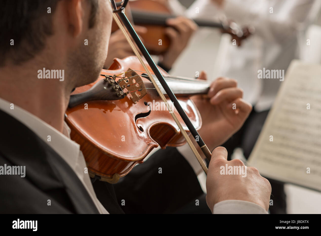 Violinist performing on stage with classical music symphony orchestra, hands close up, selective focus, unrecognizable - Stock Image