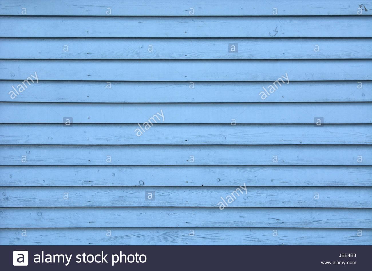Blaue Holzpaneele - Eine Wand mit blauen Schalbrettern aus Holz als Hintergrund / Kulisse / wooden backdrop in blue. - Stock Image