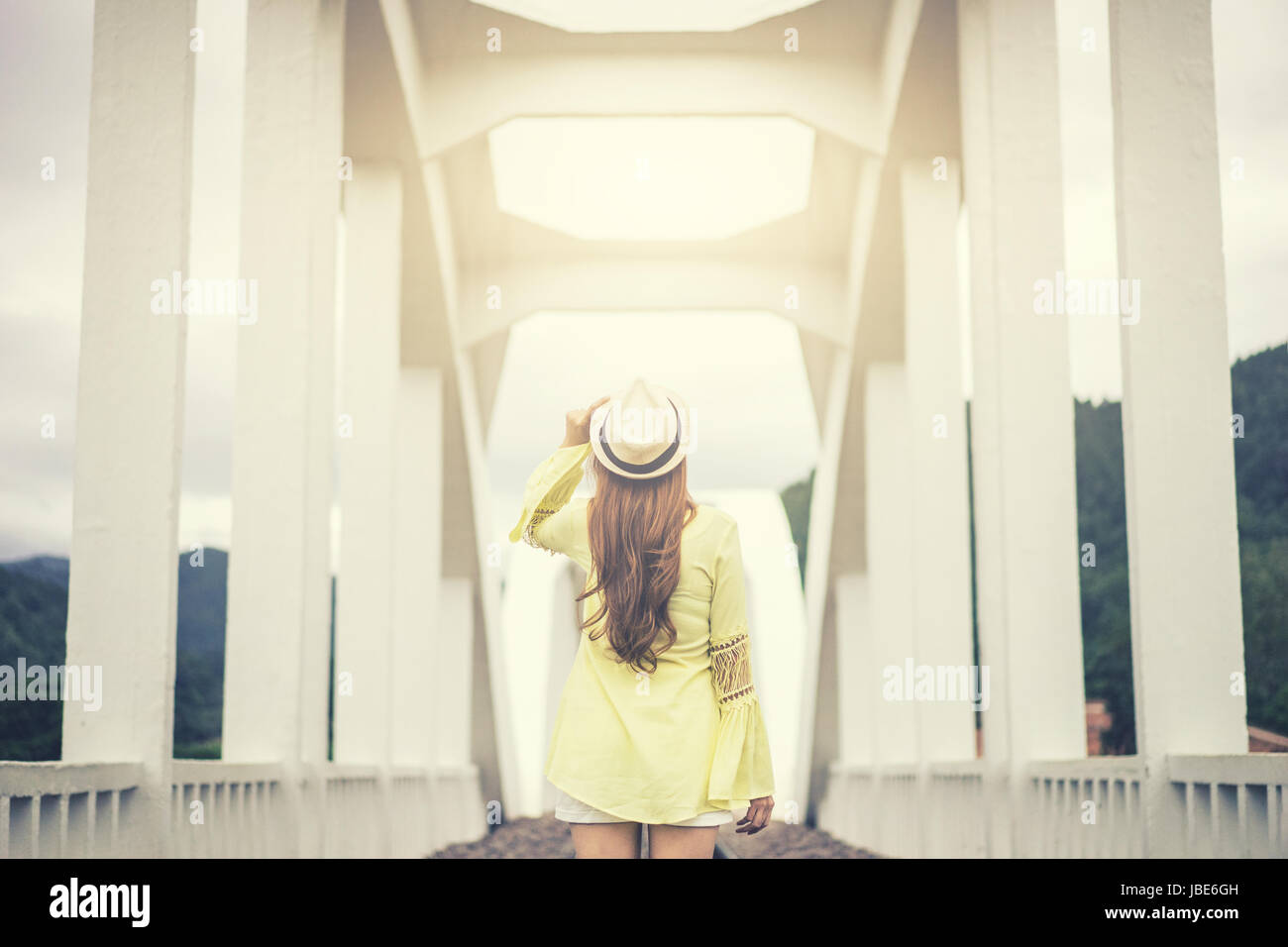 wanderlust young woman holding hat with white bridge background,travel in nature,vacation and relaxation concept.vintage - Stock Image
