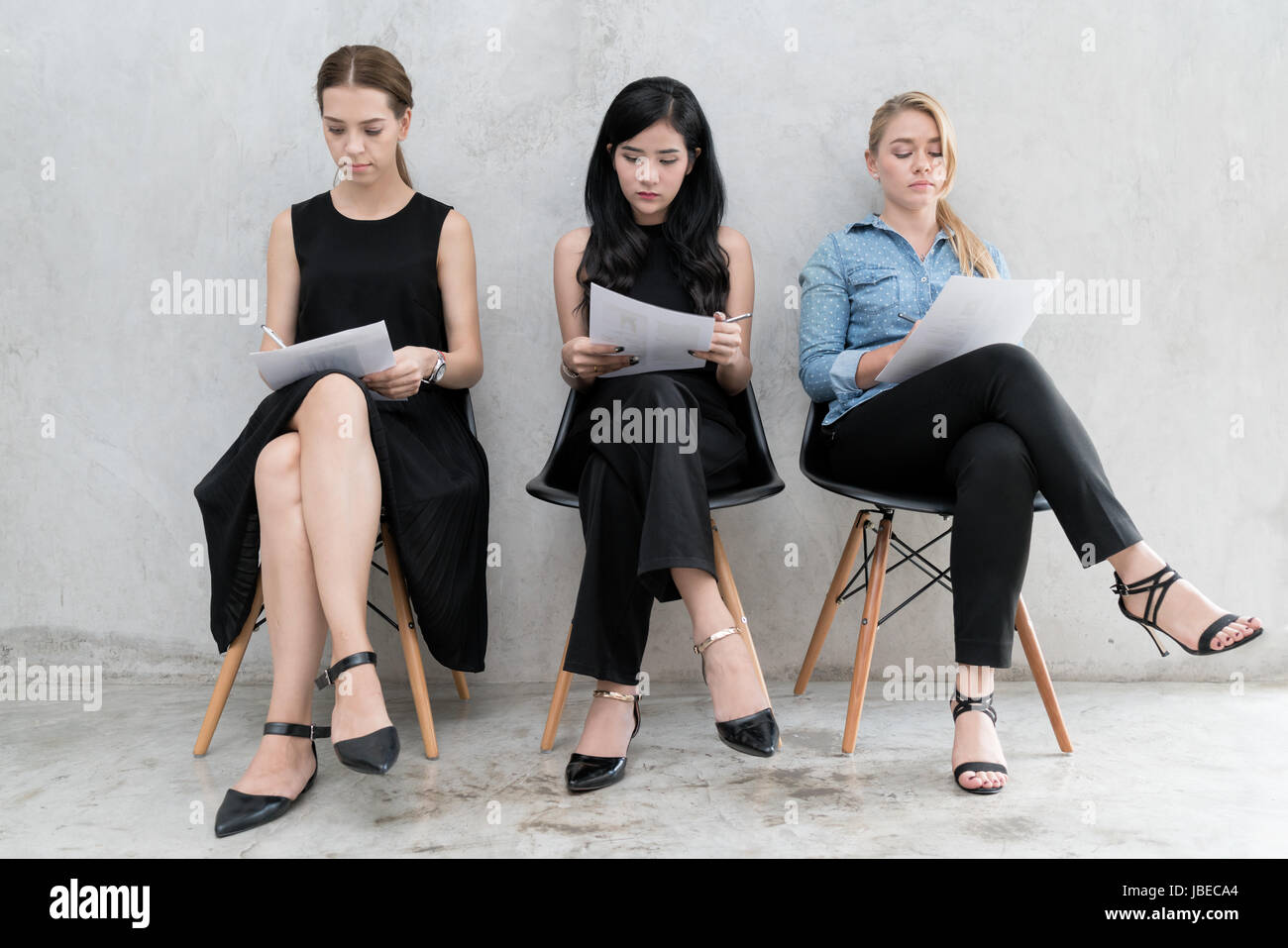 Group of asian and multiethnic business people with casual suit in queue waiting for job interview in modern office. - Stock Image