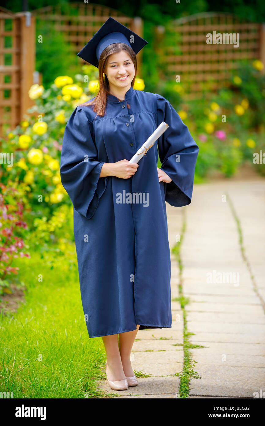 Smiling young woman holding diploma and wearing cap and gown outdoors looking at camera. Graduation concept. - Stock Image