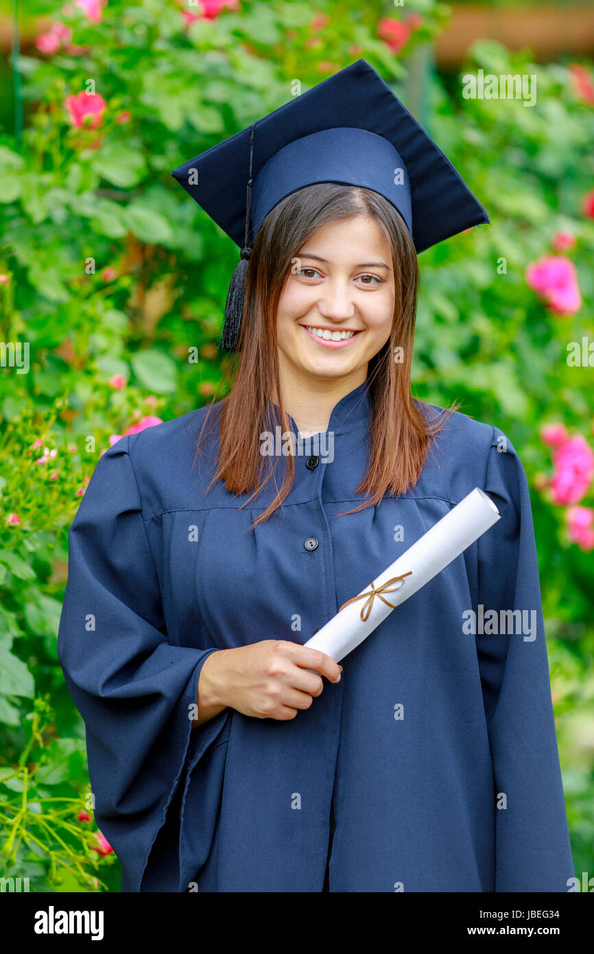 Smiling young woman holding diploma and wearing cap and gown outdoors looking at camera. Graduation concept. Stock Photo