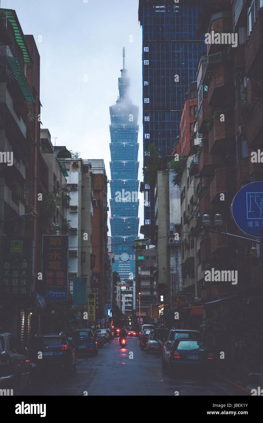 Taiwans iconic skyscraper Taipei 101 seen through a sidestreet - Stock Image